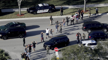 Students hold their hands in the air as they are evacuated by police from Marjory Stoneman Douglas High School in Parkland, Florida in February.