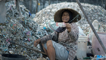 Misna, a trash picker from Ploso village in East Java, holding an Australian $20 note she found among the rubbish from the local paper company.