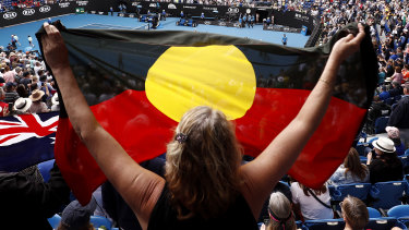 A spectator holds up the Indigenous flag as Ash Barty wins her third-round match at the Australian Open in January.
