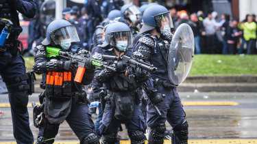 Police officers attempt to disperse protesters at a protest outside the CFMEU office on Elizabeth Street on Monday.