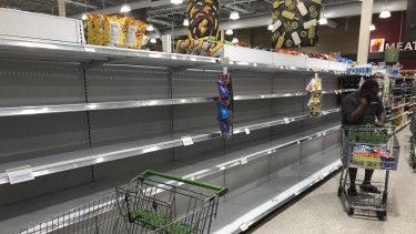 Empty shelves where water is usually stocked at a grocery store in Miami, Florida.