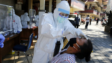 A health worker takes a nasal swab sample during public testing for the coronavirus in Bali, Indonesia.