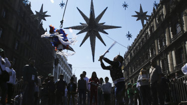 """A girl hits a traditional Christmas """"pinata""""  filled with fruit and candy during Epiphany, or Three Kings Day, January 6, celebrations at the Zocalo in Mexico City."""