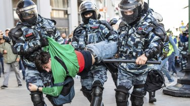 "Police detain a man during Saturday's ""unauthorised"" protest in Moscow."