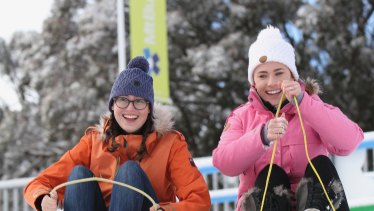 Fun times: Hope Dyson, left, and Rosie Bennett on the Village toboggan slope at Mt Buller in May.