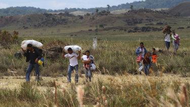 Venezuelans walk into Brazil through a field, in Pacaraima, Roraima state, Brazil.