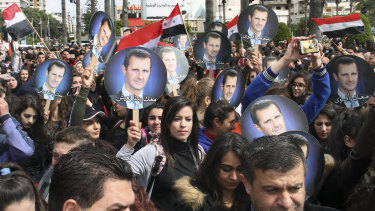 People hold Syrian flags and portraits of President Bashar al-Assad to protest US President Donald Trump stane on Israel earlier this year.