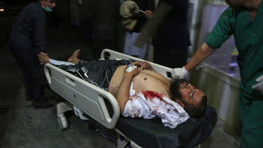 A man injured in a suicide bombing at a gathering of scholars is brought into a hospital in Kabul.