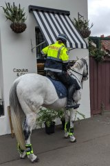 A mounted police officer stops to pick up a coffee in Brunswick, Melbourne on Tuesday.