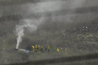 Firefighters work at the scene of the helicopter crash that killed former NBA star Kobe Bryant, his daughter and seven others.
