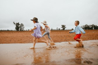 Dolly, 7, Daisy, 5, and Trader Paine, 4, enjoy some welcome rain in Narromine on Sunday.