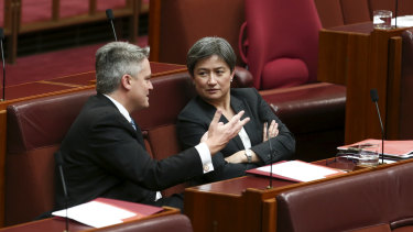 Finance Minister Mathias Cormann and Senator Penny Wong in discussion in Parliament.