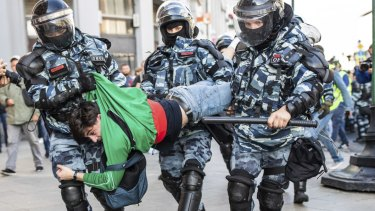 """Police detain a man during Saturday's """"unauthorised"""" protest in Moscow."""