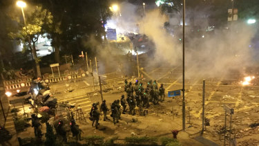 Riot police storm road in front of Polytechnic University before dawn.