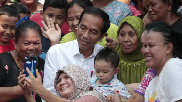Residents take a selfie with Joko Widodo prior to a speech declaring his victory in the presidential election.