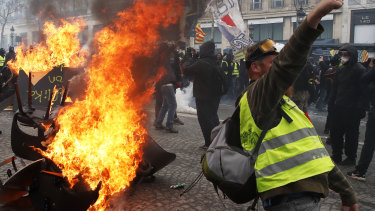 A protester shouts slogans in front of a barricade on fire during a yellow vests demonstration in Paris last month.