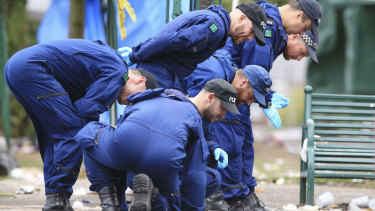 Police from the Tactical Aid Unit search for evidence at the scene of the shooting.