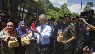 Malaysia's King Sultan Abdullah Sultan Ahmad Shah, centre, hands out food parcels to journalists camped outside the palace following the resignation of Prime Minister Mahathir Mohamad in Kuala Lumpur on Tuesday.