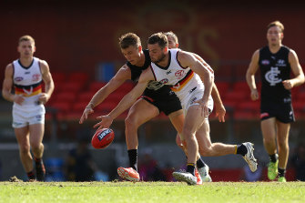 Patrick Cripps, left, and Brad Crouch, right, compete for the ball at Metricon Stadium.