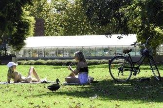Picnickers soaking up the sun at St Kilda Botanic Gardens.
