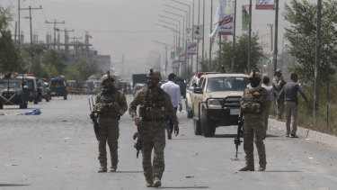 Afghan security men stand guard after the explosion near the police headquarters in Kabul, Afghanistan. The Taliban has claimed responsibility for the bombing.