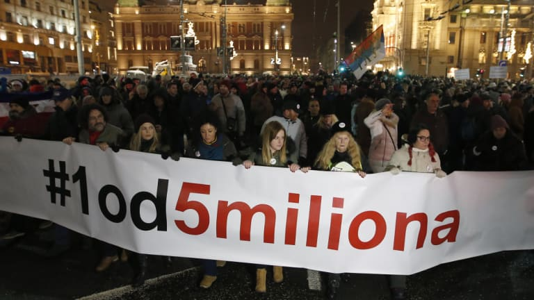 """People hold a banner that reads: """"#1 Out of 5 million"""" during a protest against populist President Aleksandar Vucic in Belgrade on Saturday."""