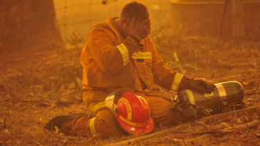 A fireman takes a breather as the the bushfire rages towards the townships of Labertouche and Tonimbuk.