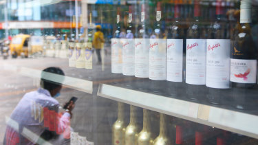 A man sits outside a wine shop that sells Australian wines in eastern Beijing's Tongzhou district.