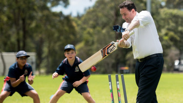 NSW Sports Minister Stuart Ayres plays with young cricketers at the Wilson Park announcement.
