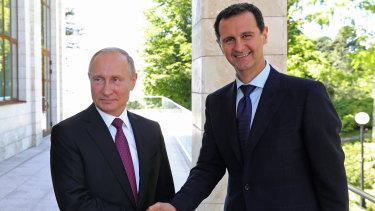 Russian President Vladimir Putin shakes hands with Syrian President Bashar al-Assad.