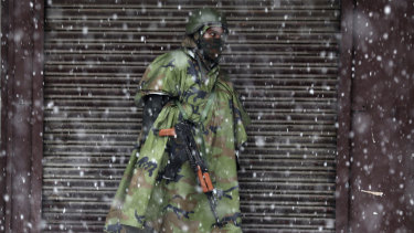 An Indian paramilitary soldier stands guard in the snow in Srinagar, Indian controlled Kashmir.