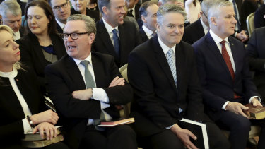 Not everyone was smiling: Turnbull supporter Christopher Pyne waits for the beginning of the ceremony beside Senator Cormann.