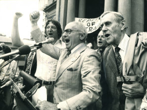 """From left: Union leader John Halfpenny, writer and academic Donald Horne and author Patrick White lead the singing of Advance Australia Fair on the steps of Sydney Town Hall in 1976. They were """"maintaining the rage"""" over the dismissal of the prime minister, Gough Whitlam, by the governor-general, John Kerr, one year earlier."""