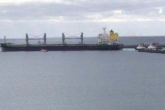 Tugboats haul on lines affixed to the grain carrier MV Medi Portland, stuck at the entrance to Portland's harbour.
