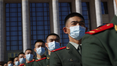 Chinese paramilitary policemen march outside the Great Hall of the People  on Friday.