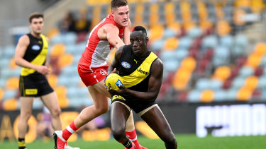 Crouching Tiger: Mabior Chol breaks through the Swans defence during the round 6 clash at The Gabba in Brisbane.