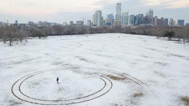 A person walks through a snow covered Zilker Park in Austin, Texas.