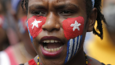 A Papuan student with her face painted with the colours of the separatist 'Morning Star' flag shouts slogans during a rally near the presidential palace in Jakarta, Indonesia.