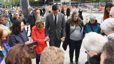 Israel Folau prays with supporters before entering mediation on Monday.