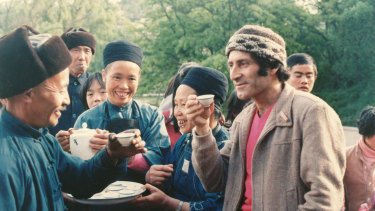Arnold Zable drinking tea in China with tribespeople near Huaxi in Guizhou Province.