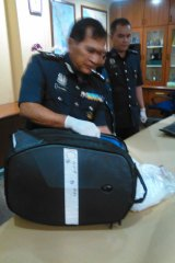 Director of Customs at Malaysia's international airport, shows the bag allegedly containing drugs that was being carried by Maria Elvira Pinto Exposto when she was arrested.