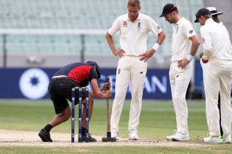 Players watch on as a groundsman attempts to flatten out the pitch on day five of the Boxing Day Test in 2017.