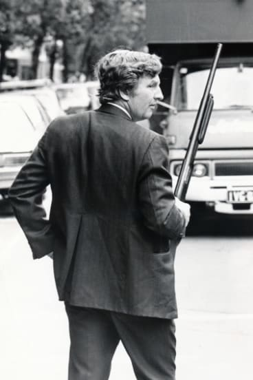A detective checks vehicles leaving the RMIT car park behind the Russell Street courts after Ray Chuck was gunned down.