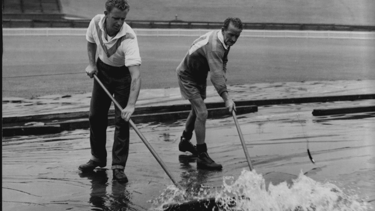 Groundsmen sweep water off the covers after heavy rains threatened to delay the Test.