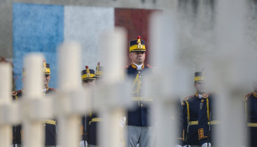 Romanian soldiers in Bucharest stand at attention next to graves of French soldiers killed in Romania during WWI.