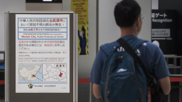 A man walks past a notice for passengers from Wuhan, China, at a quarantine station in Japan's Narita Airport.