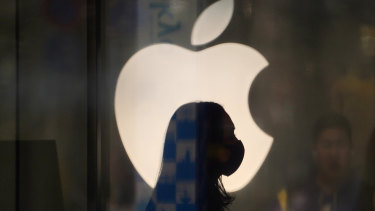 An employee wearing a protective mask in front of an Apple store, temporarily closed due to the coronavirus.