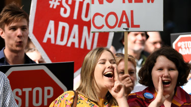 Anti-Adani protesters hold placards  in Brisbane
