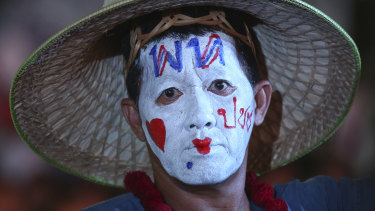 """A supporter of Pheu Thai Party wears a message on his head reading """"Pheu Thai Party love people"""" during an election campaign in Bangkok."""