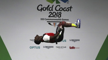 Petit Minkoumba somersaults after a lift during the 94kg weightlifting final at Sunday.